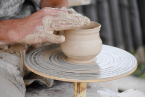 image of craftsman making vase from fresh wet clay on pottery wheel