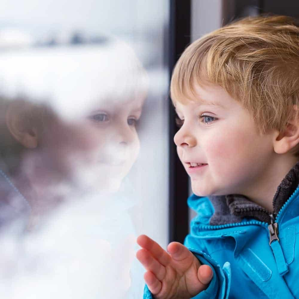 Young boy looking out the window at the snow