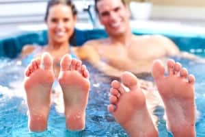 Happy couple in a Jacuzzi tub with their feet in the air.