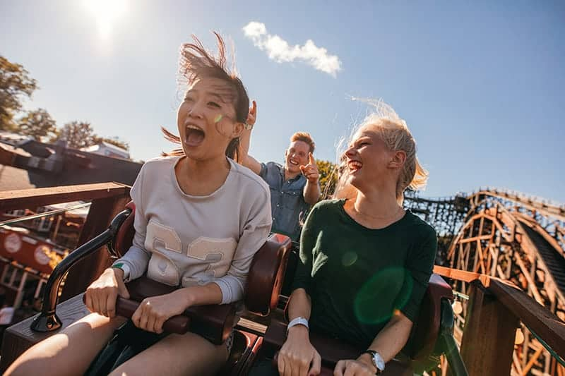 Two young girls laughing while riding wooden roller coaster at Dollywood in Pigeon Forge, Tn